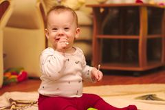 A small child is sitting on the floor in the room and playing with ear sticks. Baby, kid, kids, home, happy, young, toy, white, cute, people, fun, laughing royalty free stock photography