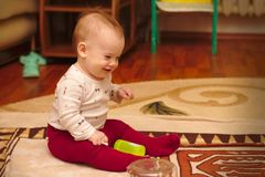 A small child is sitting on the floor in the room and playing with ear sticks. Baby, kid, kids, home, happy, young, toy, white, cute, people, fun, laughing royalty free stock photos