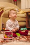 A small child is sitting on the floor in the room and playing with ear sticks. Baby, kid, kids, home, happy, young, toy, white, cute, people, fun, laughing stock photos