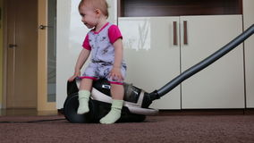 Small child sitting on the vacuum cleaner stock footage