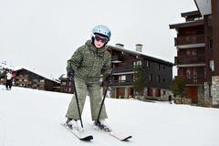 Small child skiing. In French resort on background wooden chalet Royalty Free Stock Image