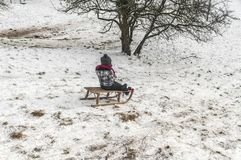Child playing in the snow with a sledge stock photos