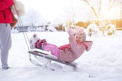A small child on a sled. Girl rolls on snowdrifts in winter, sun shines Royalty Free Stock Image