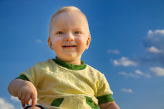 Small child smiles against the blue sky Stock Images