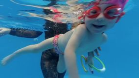 A small child smiling under water. A small child in glasses smiles swimming under water stock video