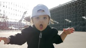 Small child son in a cap running