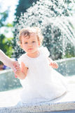 Small child and splashing fountain Stock Image
