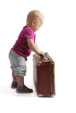 Small child standing next to a suitcase Royalty Free Stock Photo