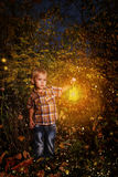 Small child standing in the night forest. Stock Photo