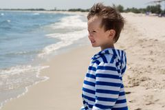A small child standing by the sea looking at the waves, Stock Photo