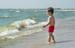 A small child standing by the sea looking at the waves, Royalty Free Stock Image