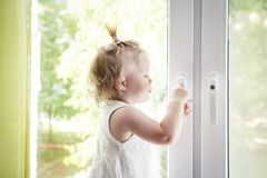 Small child is standing on windowsill and opens window. Locks on. Windows prevent children from falling out of window. Girl playing with window handle royalty free stock photo