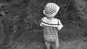 A small child stands in the garden. Near the planting of onions stock photography