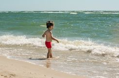 A small child stands on the seashore in the water and looks at the waves. Knows the world,. A small child stands on the seashore in the water and looks at the Royalty Free Stock Image
