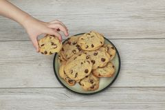 Free Small Child Stealing A Chocolate Chip Cookie From A Plate Full O Royalty Free Stock Images - 115255209