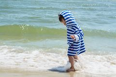A small child in a striped robe is standing on the seashore in the water and looks at his wet legs to know the world,. A small child in a striped robe is Royalty Free Stock Images