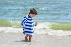 A small child in a striped robe is standing on the seashore in the water and looks at his wet legs to know the world,. A small child in a striped robe is royalty free stock image