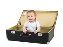 Small child in a suitcase. Small smiling child sitting in a suitcase isolated on white Stock Images