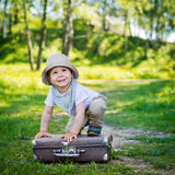 Small child on a suitcase Stock Images