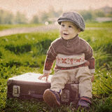 Small child on a suitcase Royalty Free Stock Image