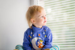 A small child with surprise looks in the window Royalty Free Stock Images