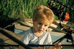 Small child with surprised face angling on river. Boy with rod on fishing pier. Summer vacation, hobby, lifestyle. Fishing, angling, activity, adventure, sport royalty free stock photos