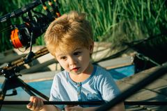 Small child with surprised face angling on river. Boy with rod on fishing pier. Summer vacation, hobby, lifestyle. Fishing, angling, activity, adventure, sport stock photos
