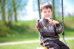 Small child on swing. In playground outdoors royalty free stock image