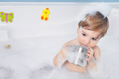 Small child takes a bath. With foam Royalty Free Stock Images