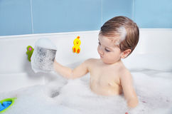 Small child takes a bath. With foam Royalty Free Stock Image