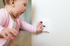 Small child touches an electrical outlet at home. Safety of children.  Royalty Free Stock Photography