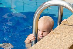Small child tries to climb out of the pool. The girl holds hands for a side and handrails. Small child tries to climb out of the pool. The girl holds hands for stock photography