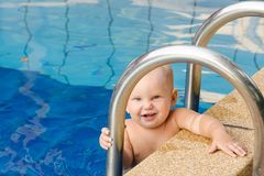 Small child tries to climb out of the pool. The girl holds hands for a side and handrails. Small child tries to climb out of the pool. The girl holds hands for royalty free stock photography