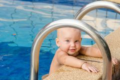 Small child tries to climb out of the pool. The girl holds hands for a side and handrails. Small child tries to climb out of the pool. The girl holds hands for royalty free stock photo