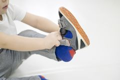 Small child tries to put on his shoes. Baby boy with shoes in hand. how to choose shoes for a child two years old. the Stock Photos