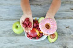 Small child trying to decide to eat fresh raspberry fruits with vitamins or delicious but unhealthy donut Royalty Free Stock Image