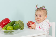 Small child with vegetables in the kitchen. Stock Photography