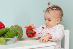 Small child with vegetables in the kitchen. Royalty Free Stock Images