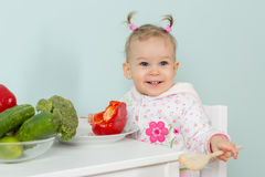 Small child with vegetables in the kitchen. Stock Image
