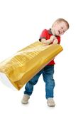 Small child waving a large paper bag for shopping. Isolated on white background Royalty Free Stock Images