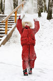 Small child in winter clothes throws snow Royalty Free Stock Images