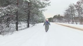 Small child in winter forest runs through snow towards camera. stock footage