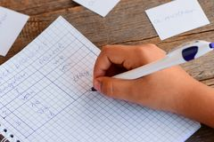 A small child is writing subject pronouns in the notebook. A notebook, a pen, paper cards with English words on a wooden table Royalty Free Stock Photo