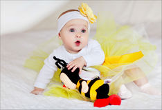 A small child in a yellow skirt sits on the bed with a toy bee.  royalty free stock image