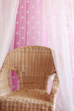 Small childish wicker chair stands next to pink wall Stock Image