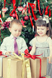 Small children and boxes with gifts Stock Photos