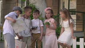 Small children the company sit on a small white fence. Small children the company walk in a retro to clothes down the street. Children in beautiful to clothes stock video footage