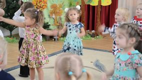 Small children dance and sing the song. A morning performance in kindergarten stock footage