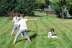 Small children do sport exercises on the grass in the park Stock Photos