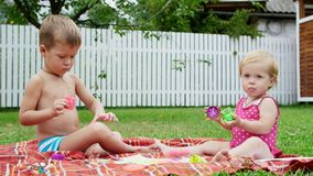 Small children, a four-year-old boy and a one-year-old girl, brother and sister, play together, paint with finger paints stock footage